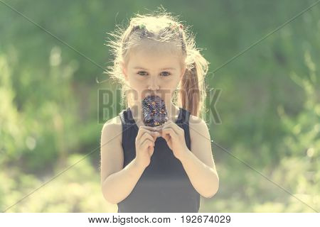 girl eating tasteful chocolate covered ice cream
