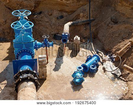 Oil, Gas, Water Industry. Wellhead With Valve Armature Underground. Dug Deep Trench