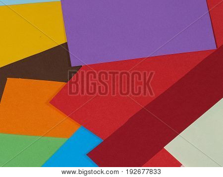Colored paper background in random arrangement flat lay