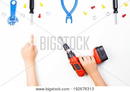 Child's hand holding drill and pointing finger to colorful toys tools on the white background.