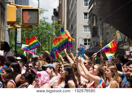 Manhattan, New York, June 25, 2017:audience with rainbow flag in The Gay Pride Parade and traffic light