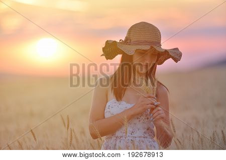 Closeup portrait of smiling young caucasian woman in wheat field. Cheerful young beautiful woman enjoying a day in natural environment at sunset