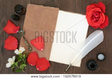 Red rose flower and petals with hemp notebook, old quill feather pen and ink, with orange blossom and essential oil bottles on old oak background.
