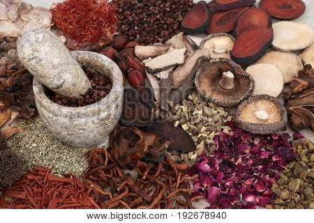 Traditional chinese herbal medicine selection with mortar and pestle forming a background.