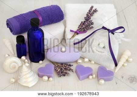 Lavender flower cleansing treatment  with moisturising cream in blue bottles, soap, face towels, cloth sponge, fragrant herb bag with decorative shells and pearls.