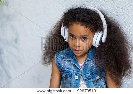 cute African girl at home listening to music in big white headphones looking at camera