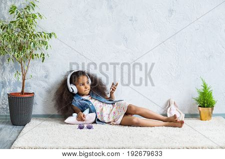 cute African girl at home listening to music in big white headphones