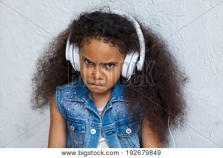 Angry African girl at home listening to music in big white headphones