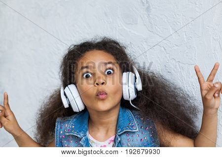 cute African girl listening to music in big white headphones looking at the camera with big eyes