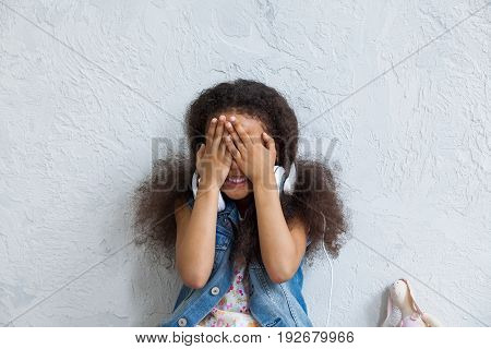 cute African girl listening to music in big white headphones Closing her face with hands and smiling