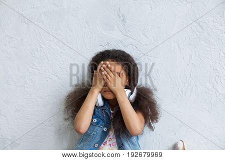 cute African girl listening to music in big white headphones Closing her face with hands