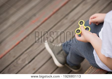 Kid boy sitting on wooden playground and playing with fidget spinner gadget - summer trend of 2017. Yellow hand spinner fidgeting hand toy rotating on child's hand