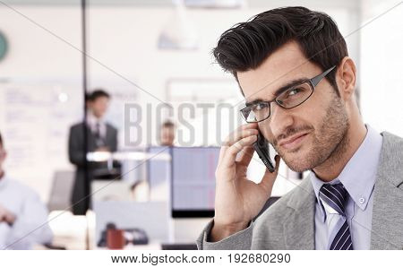 Closeup portrait of young businessman talking on mobilephone, looking at camera.