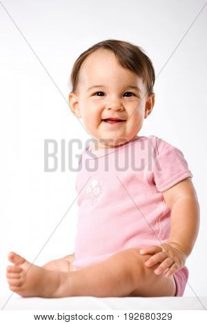 Portrait of happy sitting baby on white background.