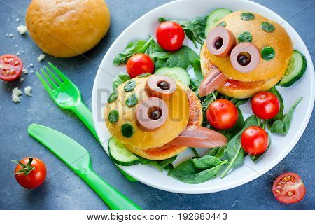 Cute frog shaped hamburger on a plate with fresh vegetables for kids party