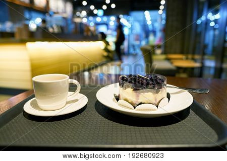 SEOUL, SOUTH KOREA - CIRCA MAY, 2017: a cup of coffee and blueberry cheese cake on a tray in Starbucks. Starbucks Corporation is an American coffee company and coffeehouse chain.