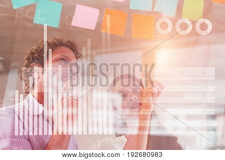 Blue data against business people looking at adhesive notes
