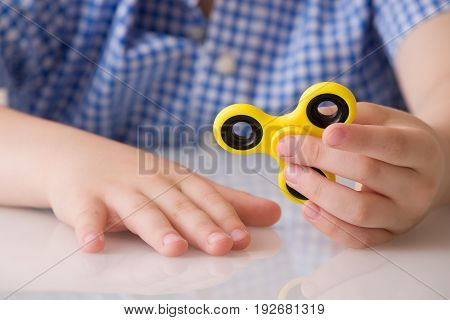 Child's hand spinning a fidget spinner device. Playing with a yellow hand spinner fidget toy