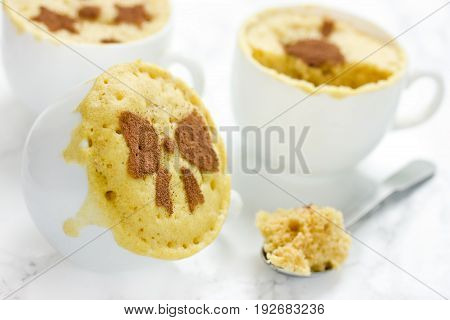 Microwave mug cake in white cups on the kitchen table
