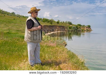 Lonely senior man standing on abrupt riverside of the Dnepr river Ukraine