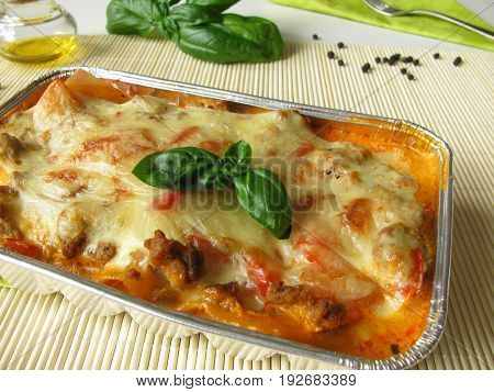 Homemade lasagne with red bell pepper and minced meat in aluminium mold