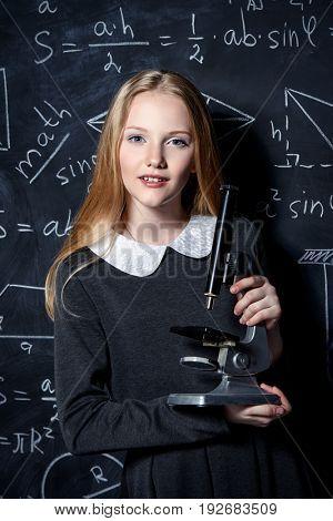 Education. Smart student girl wearing black school dress standing by a blackboard. Chalkboard background.