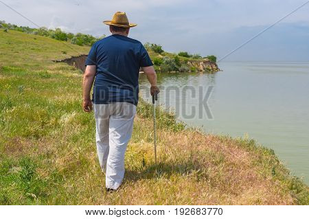 Lonely senior man in blue t-shirt and light pants walking on abrupt riverside of the Dnepr River Ukraine