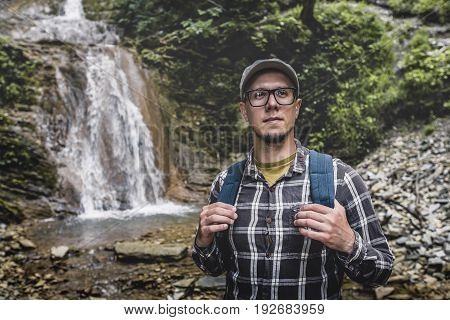 Backpacker Standing And Looking Up Near Waterfall Journey Travel destination Concept