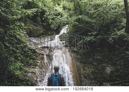 Traveler Reached Destination And Enjoys View Of Waterfall Rear View Travel Hiking Concept