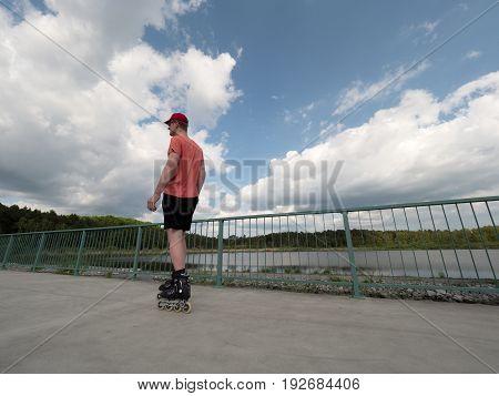 Roller Skater In Action. Man Ride In Inline Skates Ride Along Promenade Handrail, Sky In Background