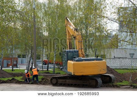 Road construction worker with a shovel in front of an bulldozer. Road repair.