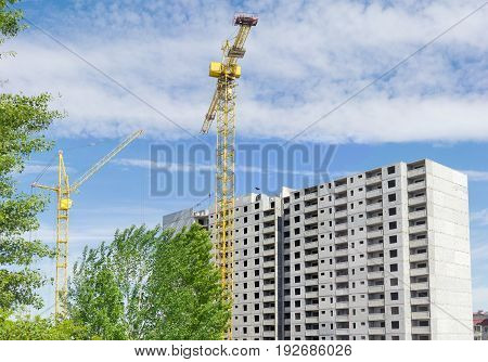 Two different tower cranes with latticed booms on the background of the upper part of a multi-story residential building under construction tree and sky