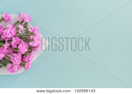 White envelope with pink beautiful flowers on a blue background. mail for you