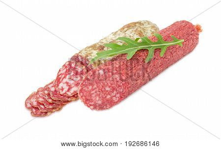 Partly cut salami and partly sliced other salami and fresh leaf of the arugula on them on a light background