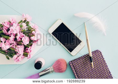 feminine flat lay on blue background, top view of woman's desktop with  envelope, flowers, pen,  nail polish, notepad and smartphone. mock up