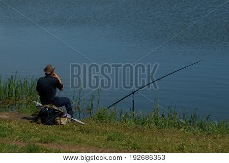 Fisherman With Fishing Rod Catching Fish, Sitting Riverside