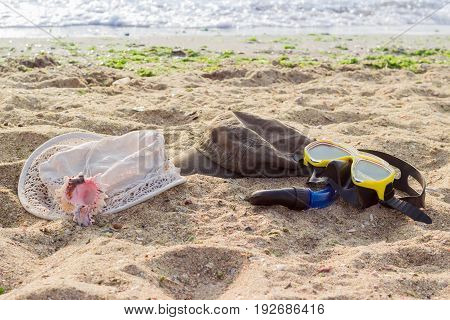 Women's hat for sun protection men's cap and black and yellow diving mask with snorkel on the sandy beach against the sea at morning
