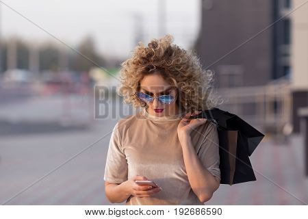 Shopping Woman Sending A Text Message On Her Cell Phone
