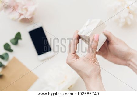 Female hands hold a white gift box on the background of flowers and phone. top view
