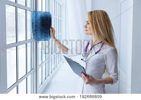 Young Professional Female Doctor Examining Patient's X-ray Of Human Spine During A Visit