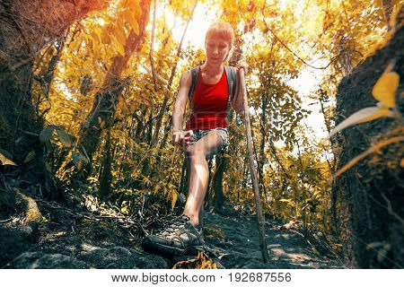 Young woman hiker applying mosquito repellent in dense tropical forest