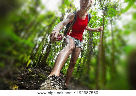 Woman hiker applying mosquito repellent on the skin in a dense tropical forest