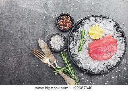 Raw tuna steak with lime, rosemary and spices served on ice over black background, top view