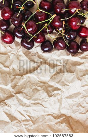 Fresh cherry berries lie on rumpled parchment paper. Concept of healthy and healthy nutrition.