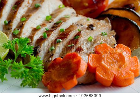 Homemade chicken breast fillet barbecue with grilled vegetables. Close-up concept of chicken breast barbecue.Sliced grilled chicken breast served with vegetable and sprinkle with chopped spring onion. Chicken steak with macro concept.