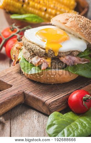 Homemmade Bacon Hamburger with fried Egg, Lettuce and lentil burger with a garnish of corn and tomatoes
