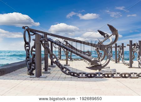 Several old anchors and anchor chains on the background of the sea and sky with clouds