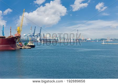 Part of the sea cargo port with several berth with different harbor cranes and bow of the ship in the foreground
