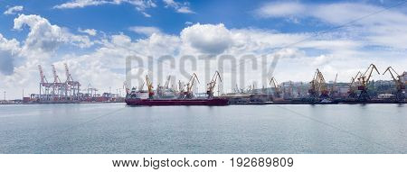 Panorama of the sea cargo port with several berth with different harbor cranes and ship standing at unloading