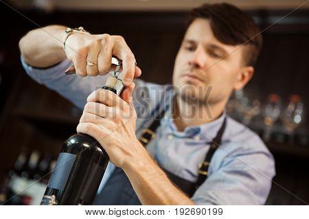 Male sommelier open wine bottle with corkscrew. Waiter with bottle of alcohol beverage and bottle-screw in hands. Bartender concentrated on uncork of elite drink at bar counter